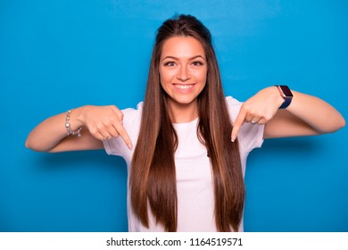 Cute brunette woman with long hair posing in white t-shirt on a blue background. Emotional portrait. She points her fingers on something, happily