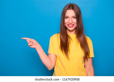 Cute brunette woman with long hair posing in yellow t-shirt on a blue background. Emotional portrait. She smiles happily with flawless white teeth and poins finger on something