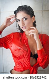 Cute brunette woman with perfect body posing in erotic pose under shower with wet hair and transparent  red shirt, perfect voluptuous body.Portrait of a joyful girl in wet shirt