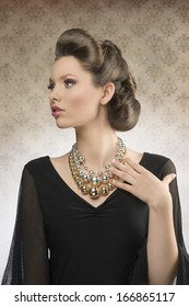 cute brunette woman posing with elegant hair-style, wearing pretty dark dress and big necklace in fashion portrait