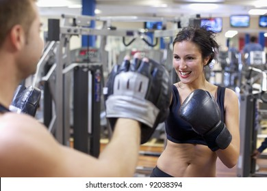 Cute brunette woman training with boxing gloves at the gym