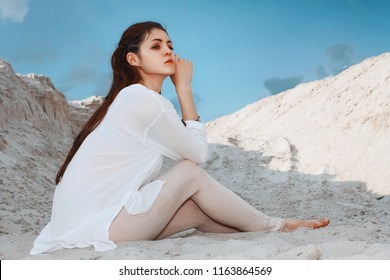 Cute brunette woman in a white blouse sitting on the sand, relaxing and posing of the desert sunny day at blue sky