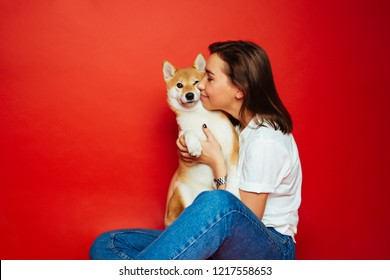Cute brunette woman in white t shirt and jeans holding and embracing Shiba Inu dog on plane red background. Love to the animals, pets concept