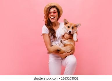 Eine süße Brunette-Frau auf weißem T-Shirt und Jeans, die einen Hund mit Corgis-Welpen auf einfarbigem Hintergrund hält und umarmt. Liebe zu den Tieren, Haustiere Konzept. fröhliche Frau, die einen walisischen Corgi Hund hält. Alles zusammen glücklich