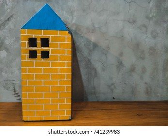 Cute building statue on bare mortar background