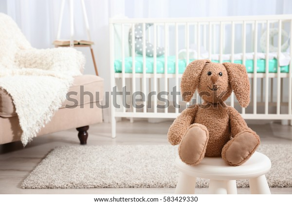 Cute bunny toy on chair in baby room