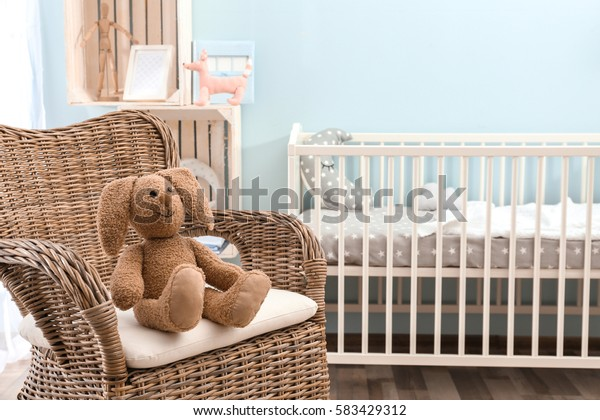 Cute bunny toy on wicker armchair in baby room