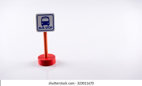 Cute Bus Stop sign on wooden post pole. Concept of traffic road sign. Isolated on white background. Slightly de-focused and close-up shot. Copy space.