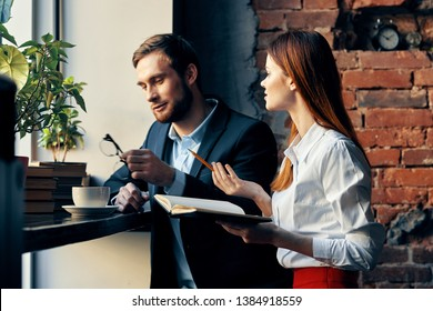Cute business man in a suit next to a woman in a cafe chatting work