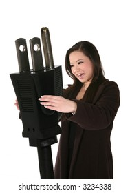 A cute business woman holding a large electrical plug