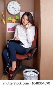 Cute businesswoman in cardboard office. Woman answers the calls and makes notes on paper. Worker professional with a smile on his face