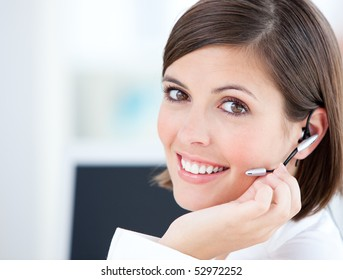 Cute businesswoman talking with clients in front of her computer in the office