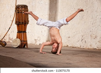 Cute capoeria boy in headstand with African music instruments