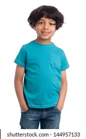 Cute casual mixed race afro caribbean boy standing isolated in studio white background and blue tee shirt.