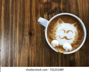 Cute cat face latte art coffee in white cup on wooden table ; love coffee, Cute Neko latte art coffee
