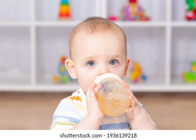 Cute caucasian baby boy drinking from bottle fruit tea. Sitting on white carpet in striped bodysuit. Different children's toys in the background. Looking to the camera.