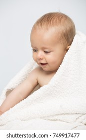 Cute caucasian baby boy sitting on a bed with a white towel wrapped around him after bath time.
