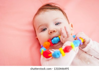 Cute Caucasian baby girl taking into her mouth a teething toy. First tooth concept illustrative image.