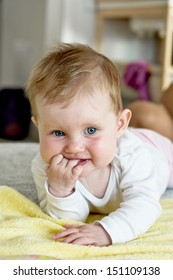 Cute caucasian baby lying on stomach and looking around.