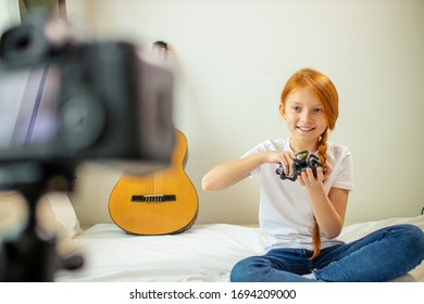 cute caucasian blogger child girl show new device at camera, girl talk about new technologies, toys and modern devices, she loves being useful for audience