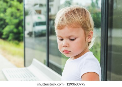 Cute Caucasian blond baby girl sits on a bus stop. Close-up outdoor portrait