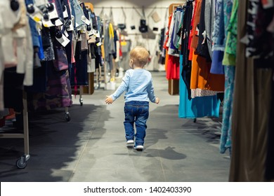 Cute caucasian blond toddler boy walking alone at clothes retail store between rack with hangers. Baby discovers adult shopping world. Baby get lost at big hypermarket shopping mall