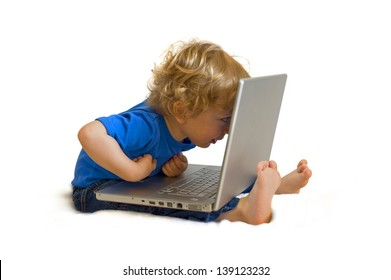 Cute caucasian boy child full lenght with laptop computer on his lap dressed in blue shirt and jeans, sitting on the floor and pointing interested isolated on white background