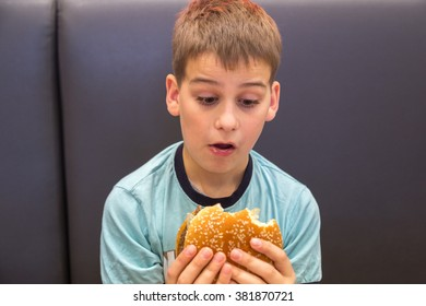 Cute caucasian boy is eating big burger