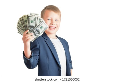 Cute caucasian boy is holding a fan of a pack of hundred-dollar bills, smiling and looking at the camera isolated on a white background with copy space. Successful businessman.