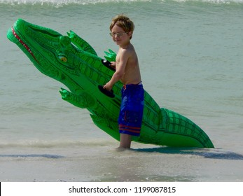 A cute caucasian boy stands in tropical water holding a large, blow-up alligator floatation device.