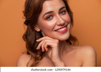 Cute caucasian brunette woman with curly hairstyle on orange background. Fresh clean skin with evening make up and freckles. Hands near her face. Close up portrait
