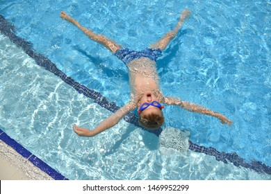 Cute Caucasian child boy in goggles and swimming trunks is swimming backstroke in swimming pool with blue water face-up. View from the top. Active healthy lifestyle, water sport activity on summer