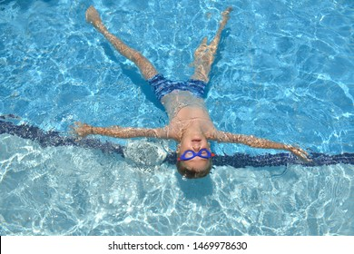 Cute Caucasian child boy in goggles and swimming trunks is swimming backstroke in swimming pool with blue water face-up. View from the top. Active healthy lifestyle, water sport activity on summer.