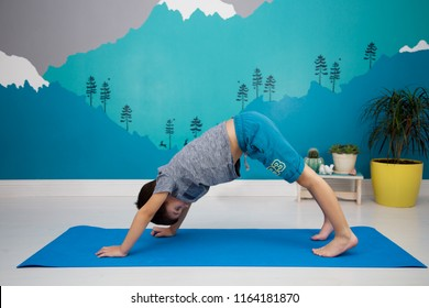 A Cute caucasian child does yoga, downward facing dog position, in a beautiful turquoise  room with mountain mural. Adho Mukha Svanasana