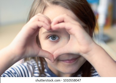 A cute Caucasian child holds a palm in the shape of a heart.