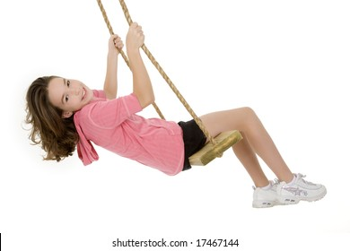 Cute Caucasian child playing on a wooden swing isolated on a white background