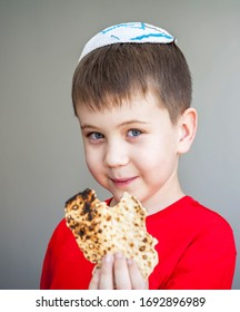 Cute Caucasian child in a white kippah cap eating a piece of shmura matzo, traditional Jewish unleavened bread for Pessakh, Jewish Passover holiday.