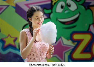 Cute caucasian girl in amusement park is eating pink candyfloss. Portrait of happy attractive young woman with cotton candy.