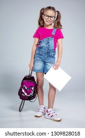 Cute caucasian girl in glasses with sequin backpack and white textbook - empty cover for mock up template