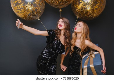 Cute caucasian girl with long curly hair posing with kissing face expression, holding big gift. Relaxed young woman making selfie with friend on dark background during christmas celebration.