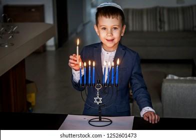 Cute Caucasian Jewish boy lighting candles on a traditional Hanukkah menorah candelabrum, Jewish holiday Chanukah concept.