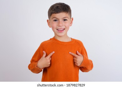 Cute Caucasian kid boy wearing knitted sweater against white wall points at his body, being in good mood after going shopping and making successful purchases