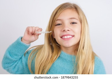 Cute Caucasian kid girl wearing blue knitted sweater against white wall holding an invisible braces aligner. Dental healthcare concept.