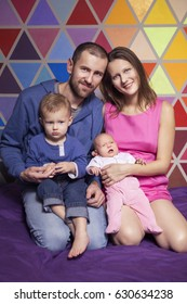 Cute caucasian ordinary family in casual clothes at home sitting on a couch. Lifestyle portrait of mom, dad, two years old son and newborn daughter