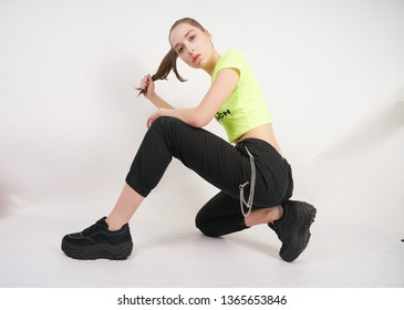 cute caucasian teen girl in green t-shirt and black sweatpants with platform sneakers posing on white background in Studio