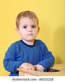 Cute caucasian toddler missing his mum in kindergarten.