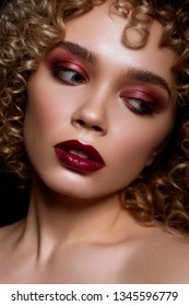 Cute caucasian woman with afro (curls) hairstyle on a dark background. She wears dark evening (or podium) make up with red mascara on her eyes ans lips