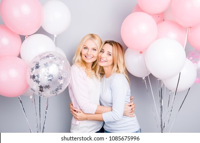 Cute charming cheerful lovely mother and daughter hugging enjoying white pink decoration air balloons surprise gift present festive mood trust support understanding isolated on grey background