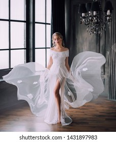 Cute charming girl collected blond in long white flying waving vintage evening dress open shoulders hair long open leg, mysterious young princess ghost gloomy gothic castle. retro style Wedding bride