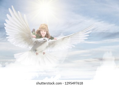 Cute charming little boy flying on the wings of a beautiful white bird up in the bright sky, Child game and imagination concept